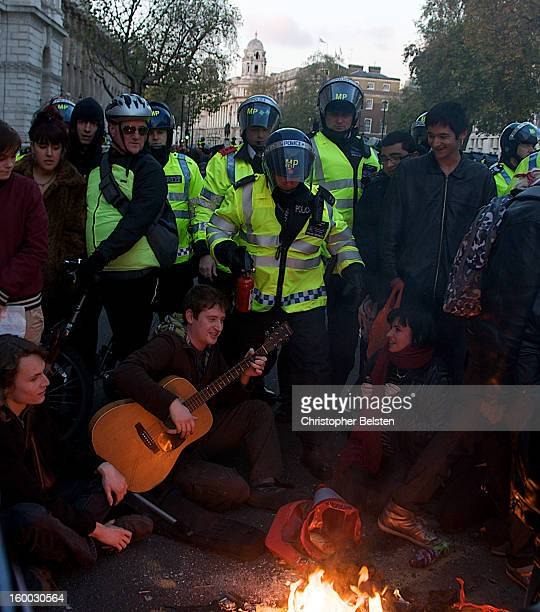 Students playing guitar and sitting in protest on Whitehall, London during the G20 demonstrations as police attempt to extinguish fire