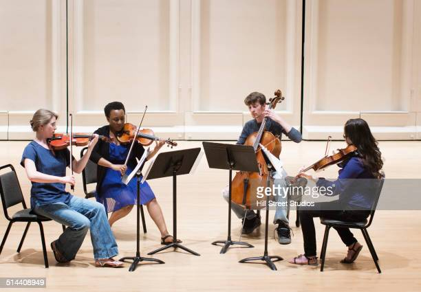 students playing in college string quartet - musical quartet stock photos and pictures