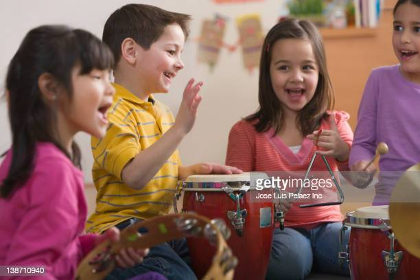 students playing musical instruments in classroom - triangle percussion instrument stock photos and pictures