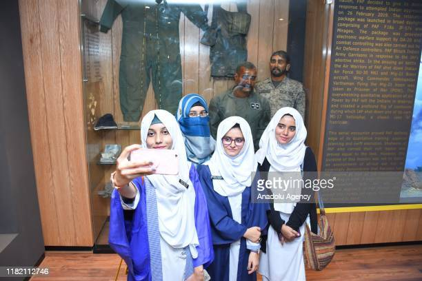 Students pose for a selfie in front of the Statue of Indian pilot Abhinandan after his MiG21 fighter aircraft plane was shot down by the Pakistan Air...