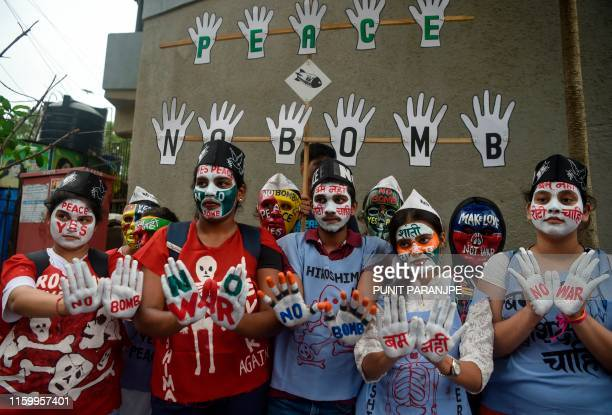 Students pose showing their faces and hands painted with slogans for peace during a rally to mark Hiroshima Day, in Mumbai on August 6, 2019. - The...