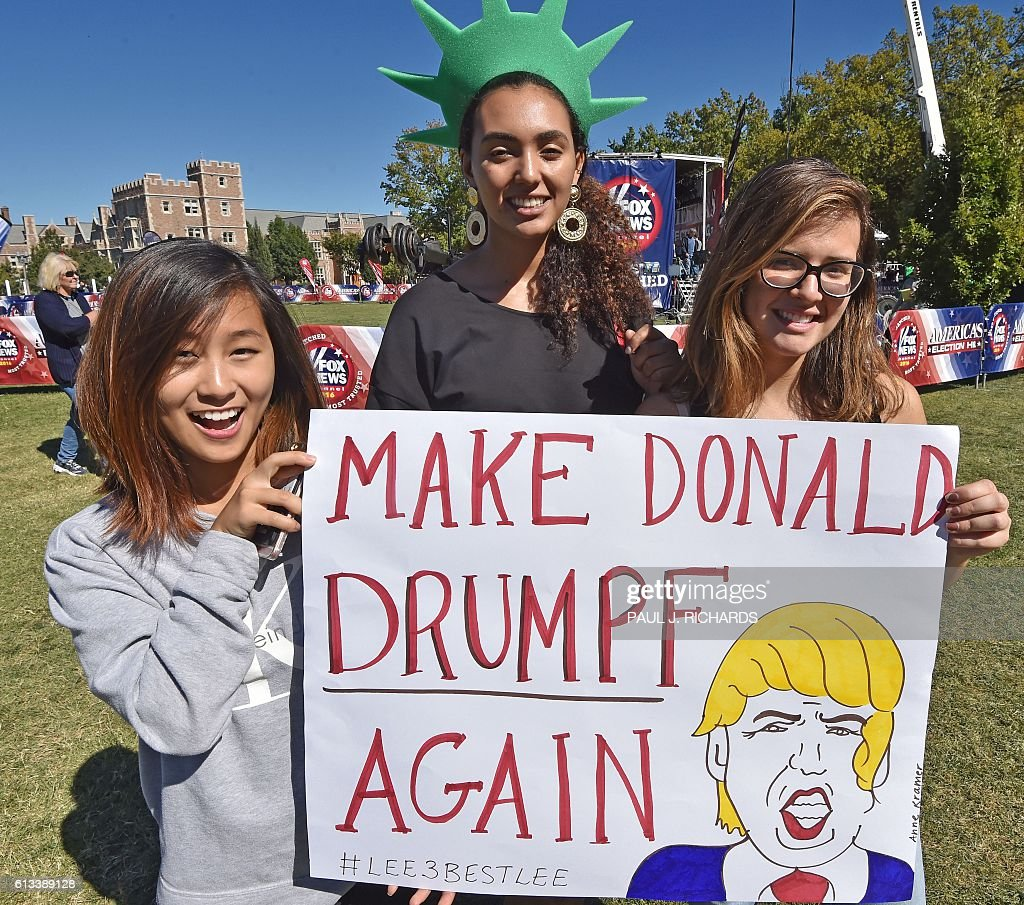 Students pose with their sign outside the site of the second US Presidential debate, on October 8, 2016, at Washington University in St. Louis, Missouri. US Presidential Republican nominees Donald Trump and Democrat nominee Hillary Clinton will debate for the second time in St. Louis on October 9. / AFP / PAUL