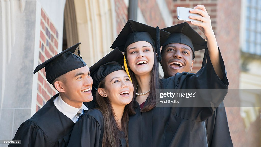 Students posing for cell phone selfie at graduation : Stock Photo