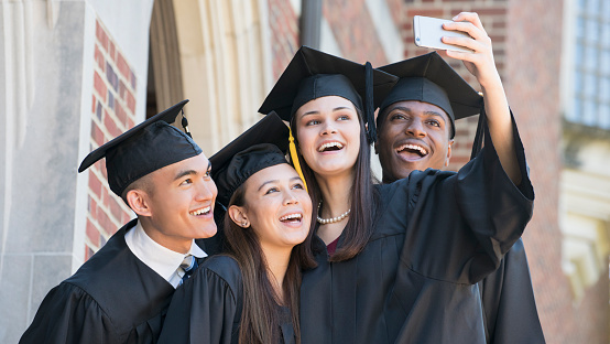 Students posing for cell phone selfie at graduation - gettyimageskorea