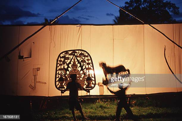 Students practice traditional shadow puppetry in a grassy field at Wat Bo in Siem Reap town Traveling puppet shows depicting stories from the...