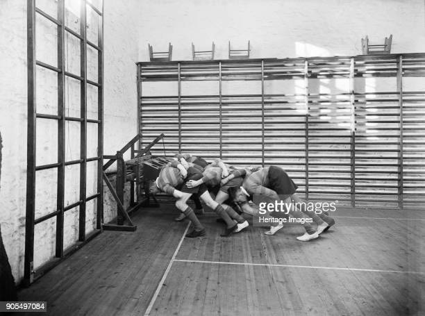 Students practicing rugby scrummaging, Launceston College, Cornwall, 1930s. Pupils using a wall mounted scrummage machine in the school's gymnasium....