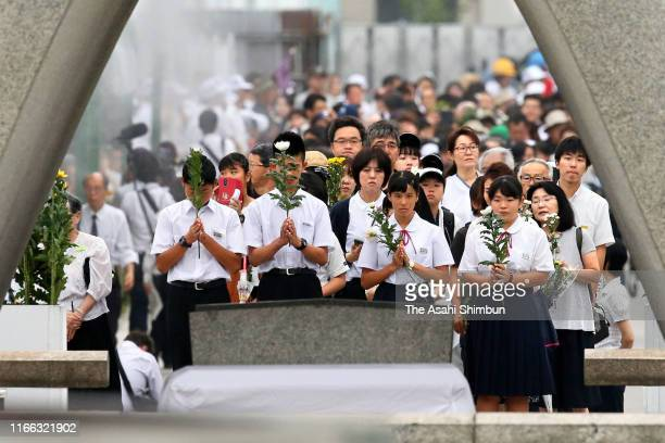 Students pray for the victims in front of the cenotaph during the Peace Memorial Ceremony on the 74th anniversary of the atomic bombing of Hiroshima...