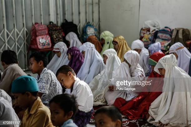 Students pray inside the classroom at MASTER school on February 20 2014 in Depok West Java Indonesia The school is known as Masjid Terminal school or...