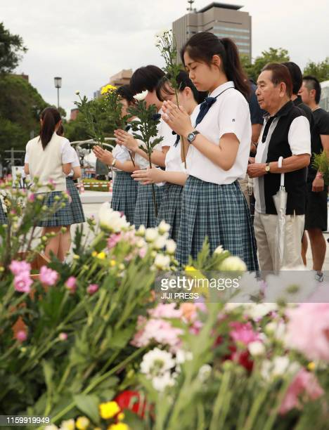 Students pray to mourn victims prior to the 74th anniversary of memorial service for atomic bomb victims at the Peace Memorial Park in Hiroshima on...