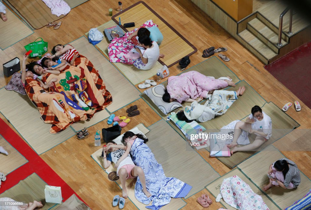 Students prepare to sleep on mats laid out on the floor inside a gymnasium at Huazhong Normal University on June 21, 2013 in Wuhan, Hubei province of China. About 600 students slept inside the gymnasium to keep cool in Wuhan which reached 35 degrees Celsius (95 degrees Fahrenheit) on Saturday. The university turned on the air conditioner in the gymnasium and provided more than 450 mats for the students.