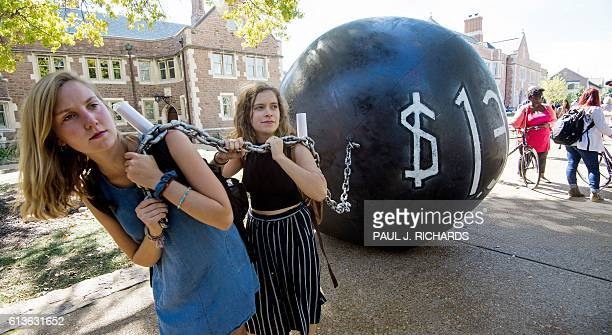 Students pull a mock ball chain representing the $14 trilling outstanding student debt at Washington University in St Louis Missouri where second...