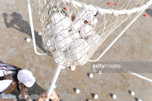 Students putting balls into a basket