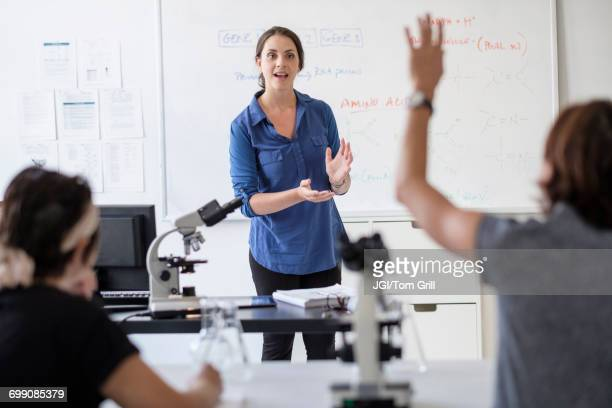 students questioning professor in classroom - college professor stock photos and pictures