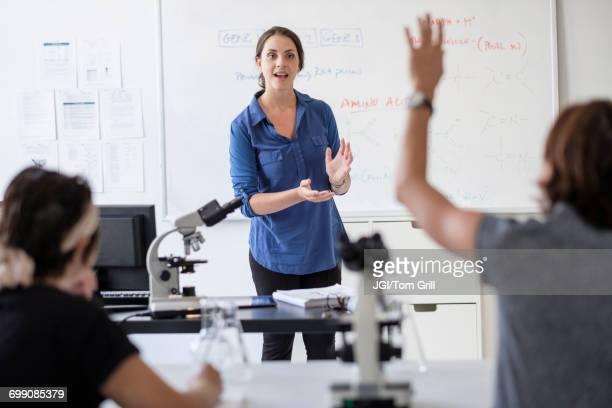 students questioning professor in classroom - enseignante photos et images de collection