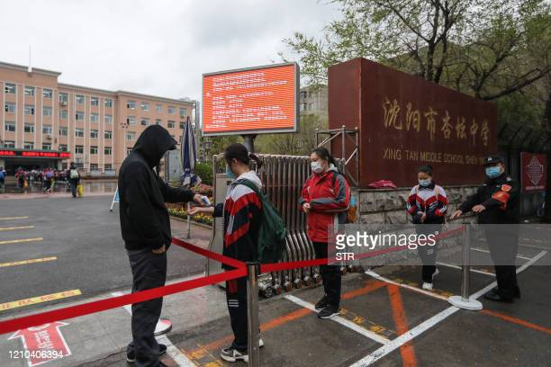 Students queue at a distance outside a middle school while waiting to be checked body temperature checked as students return to school after the term...