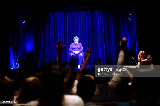 Students raise their hand as they direct questions to Holocaust survivor Adina Sella as she is displayed on a threedimensional hologram at the Take A...