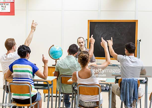Students raise their hands to answer during a lesson
