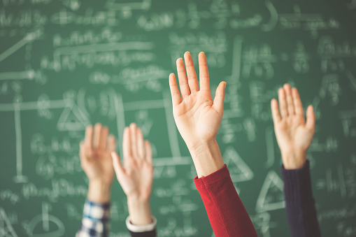 Students raised up hands green chalk board in classroom 944043026