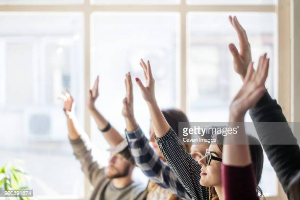 students raising hands during lesson in classroom - arms raised stock pictures, royalty-free photos & images