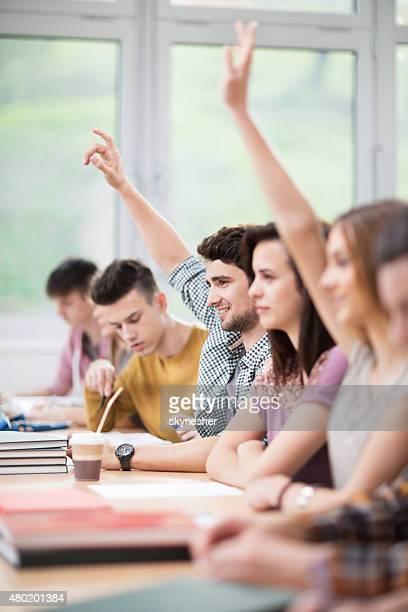 Étudiants placer les mains, afin de répondre à la question au cours de la lecture.
