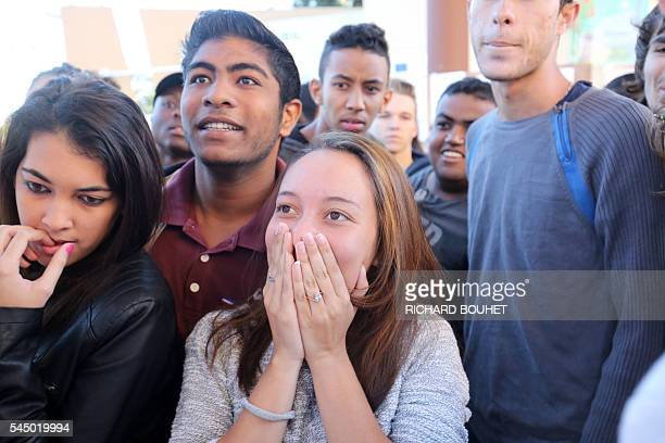 Students react after viewing the results of the baccalaureat exam on July 5, 2016 at the Moulin Joli high school in La Possession, in the French...