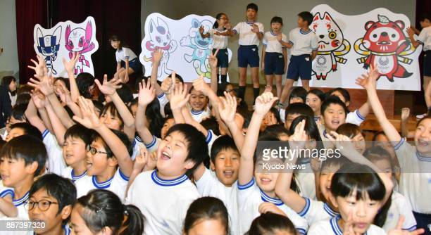 Students react at Kakezuka elementary school in Tokyo on Dec 7 after organizers of the 2020 Tokyo Olympics and Paralympics unveiled three pairs of...