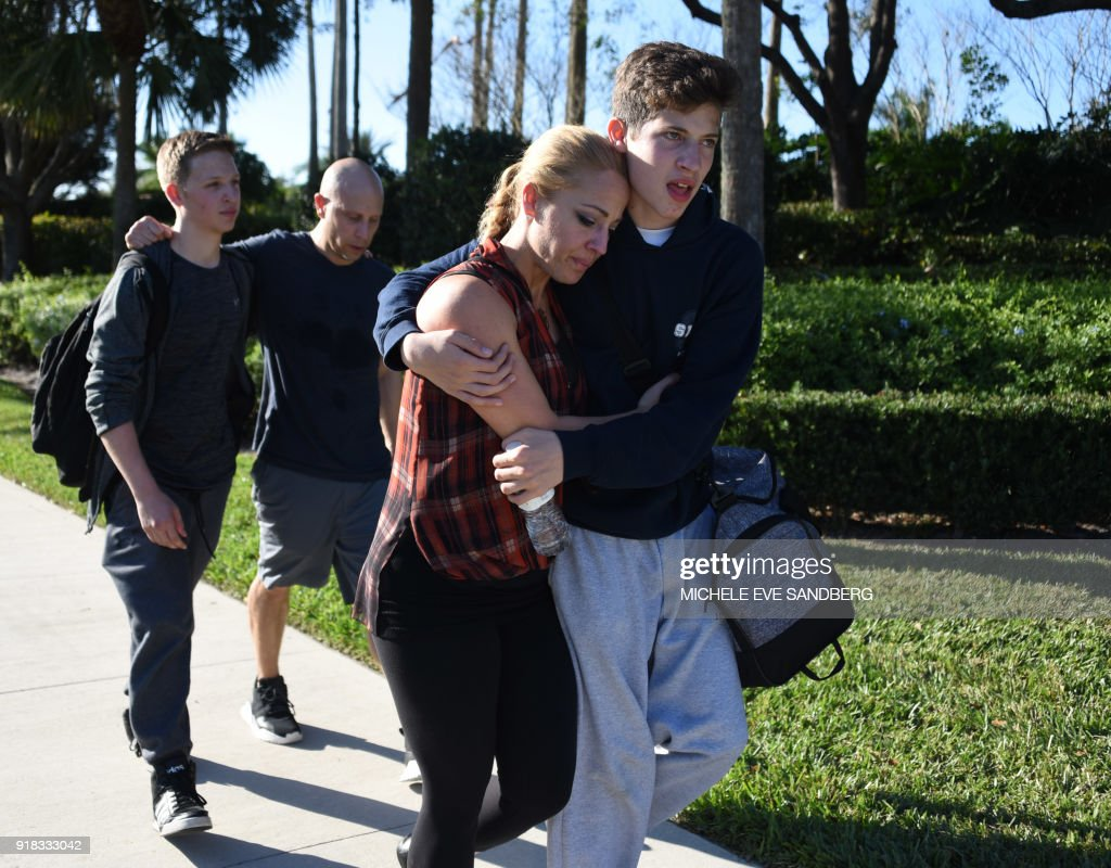 TOPSHOT - Students react following a shooting at Marjory Stoneman Douglas High School in Parkland, Florida, a city about 50 miles (80 kilometers) north of Miami on February 14, 2018. A gunman opened fire at the Florida high school, an incident that officials said caused 'numerous fatalities' and left terrified students huddled in their classrooms, texting friends and family for help. The Broward County Sheriff's Office said a suspect was in custody. / AFP PHOTO / Michele Eve Sandberg