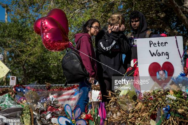 Students react to a memorial outside Marjory Stoneman Douglas High School during the ENOUGH National School Walkout rally in Parkland Florida US on...