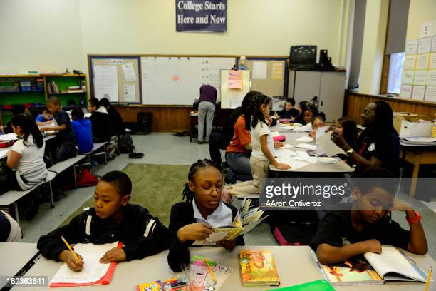Students read and do other homework activities as Rev. Leon Kelly and other volunteers help out during Open Doors after school program at Wyatt...