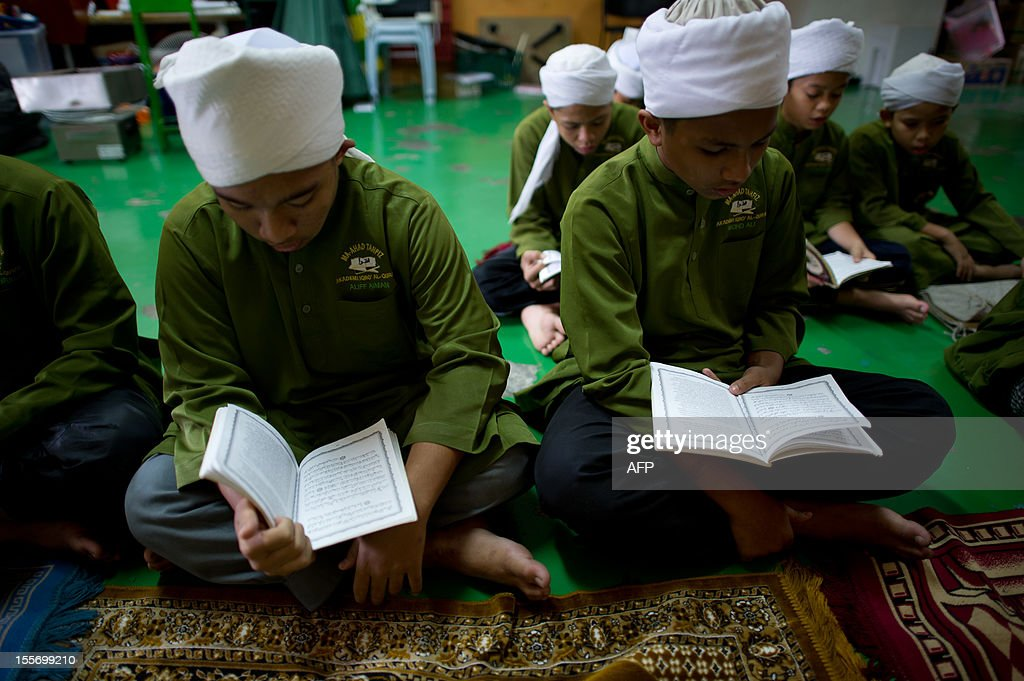 Students read copies of the Koran at the Iqro Al-Quran Bestari academy for the orphanage in the suburbs of Kuala Lumpur on November 7, 2012.