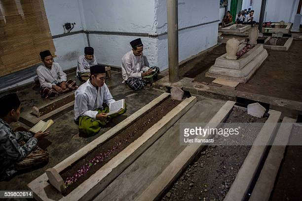Students read the Quran at ancestral graves at the islamic boarding school Lirboyo during the holy month of Ramadan on June 10 2016 in Kediri East...