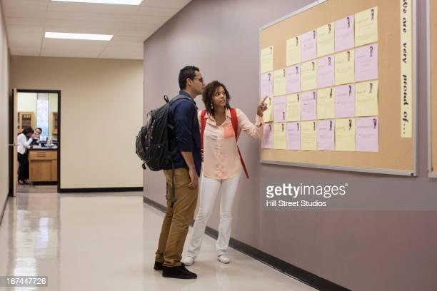 Students reading bulletin board in hallway