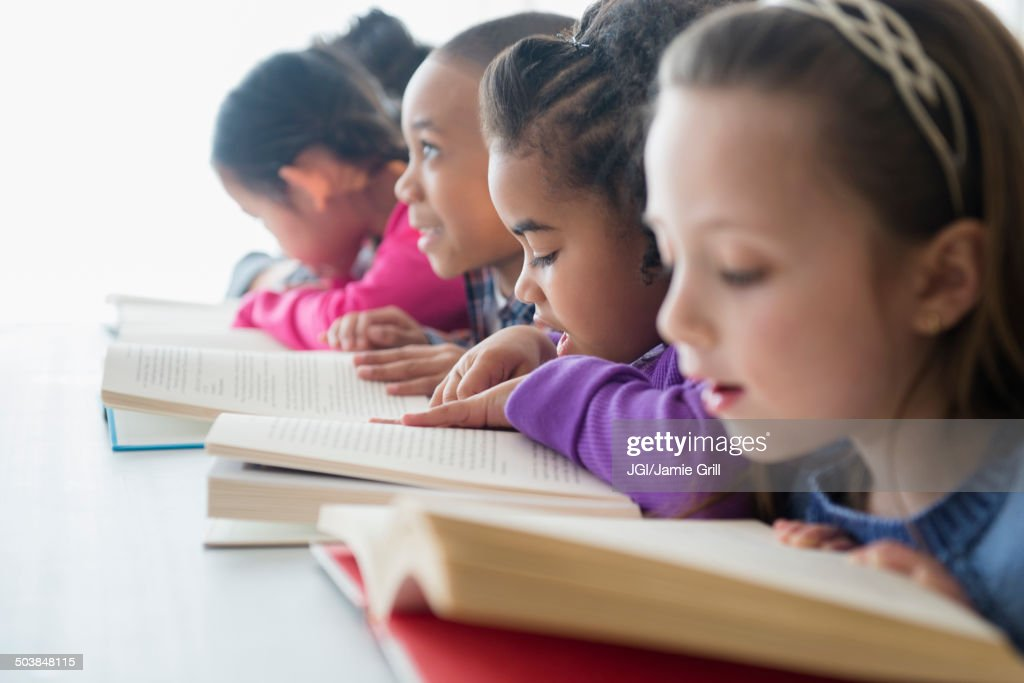 Students reading in classroom : Stock Photo