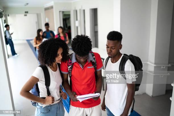 alunos lendo algo no bloco de notas no corredor - patio de colegio - fotografias e filmes do acervo