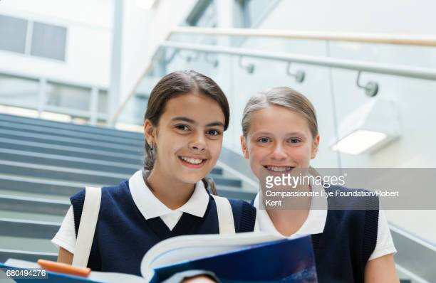 Students reading text book on stairs