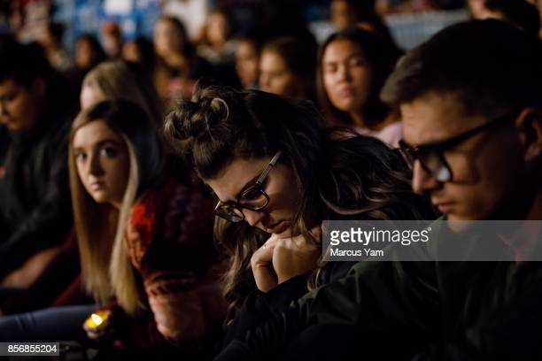 UNLV students reflect on words of wisdom dispersed during a candle light vigil for the victims of the mass shootings that killed 59 people and...