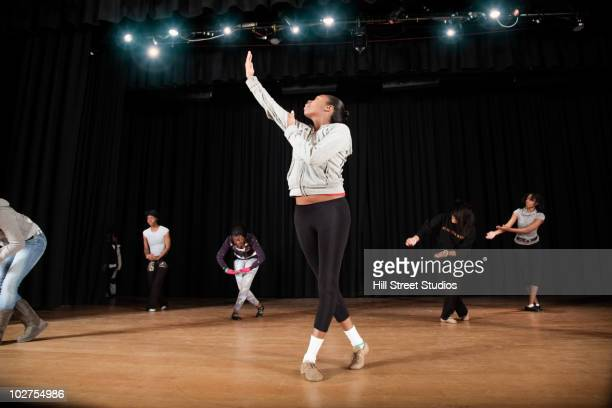 Students rehearsing dance on high school stage
