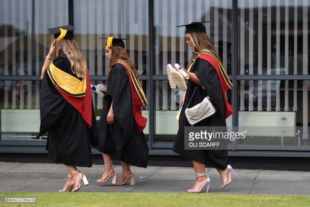 Students relax on campus at the University of Bolton after receiving their degree certificates in a Covid-safe, in-person graduation ceremony one of...