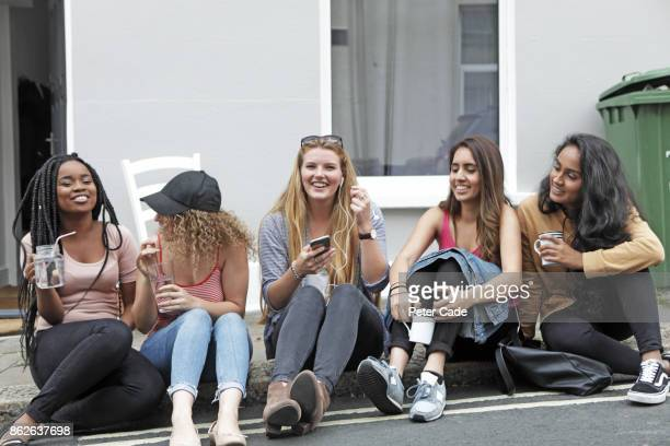 Students relaxing outside house