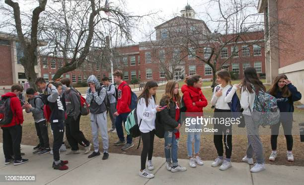 Students released from Wellesley Middle School in Wellesley MA wait outside for parents to pick them up in front of the school on March 6 2020 A...