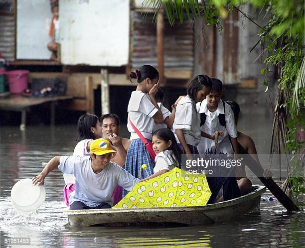 Students ride an improvised canoe transporting them home after classes were suspended due to flooding in Malabon city suburban Manila 01 September...