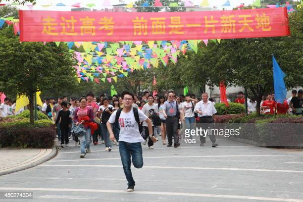 Students run as they leave the examine room after the first subject of the National College Entrance Examination at No1 High School of Quanzhou...