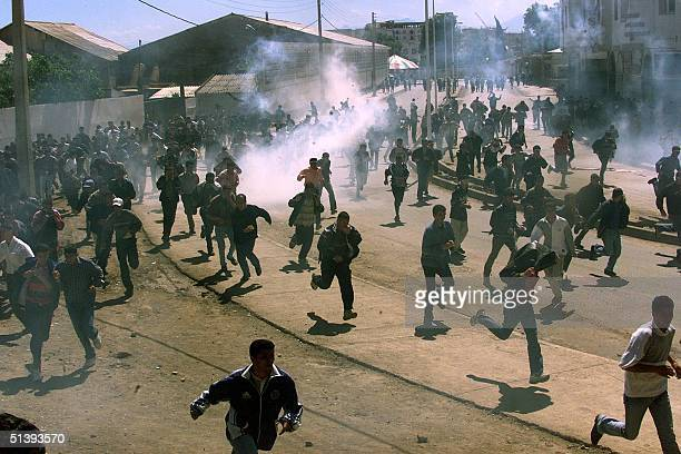 Students run for cover 29 April 2001 in the Berber town of Bejaia northeastern Algeria after violent clashes with riot police which followed a...