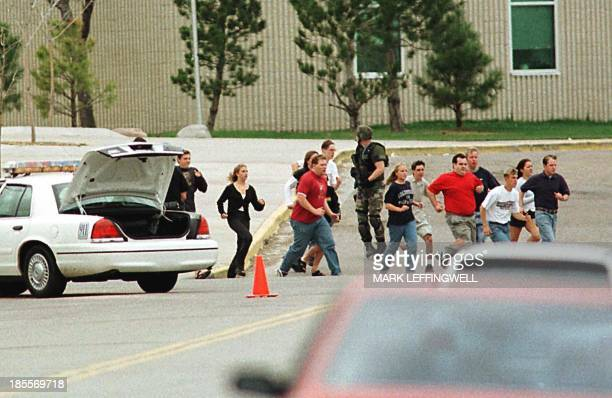 Students run from Columbine High School run under cover from police 20 April 1999 in Littleton Colorado after two masked teens on a suicide mission...