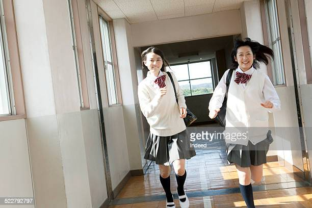 2 students running along a corridor