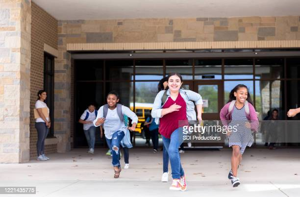 students running from school building - state school stock pictures, royalty-free photos & images
