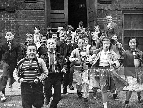 Students rushing out of the school building for summer vacation after the last day of classes, June 1954.