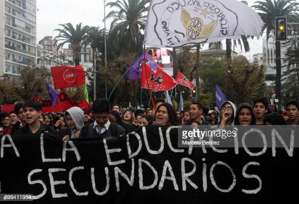 Students shout slogans and display a flag during a national demonstration organized by the Confederation of Students of Chile to demand free and...