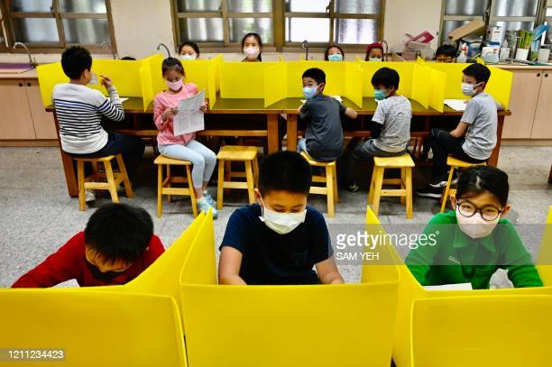 Students sit at desks with plastic partitions as a preventive measure to curb the spread of the COVID19 coronavirus during a lesson at Dajia...
