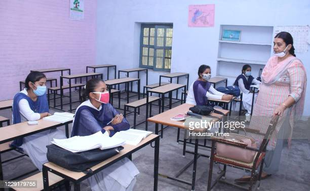Students sit distantly while attending a class after schools partially reopened during coronavirus outbreak, at Government Girls' Senior Secondary...